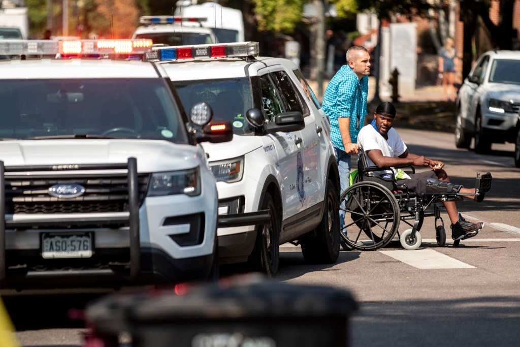 Chris Richardson, an outreach worker with the Mental Health Center of Denver, pushes a man across 14th Avenue, away from an encampment in front of Morey Middle School that's being swept by authorities. Capitol Hill, Aug. 6, 2020.