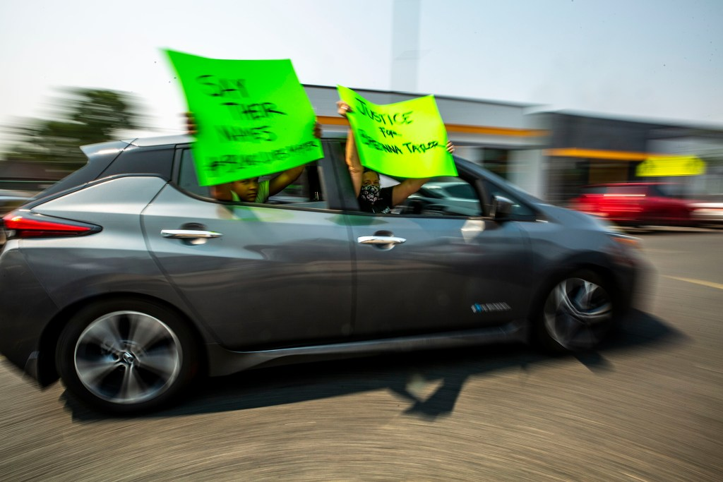 Activists drive a circle around Brother Jeff's Cultural Center, honking and holding signs demanding justice for Elijah McClain and Breonna Taylor. Aug. 22, 2020.