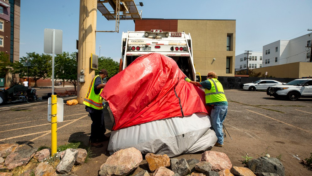 City workers throw a tent into a garbage truck at the end of a forced cleanup at Park Avenue and Curtis Street in Five Points. Aug. 26, 2020.