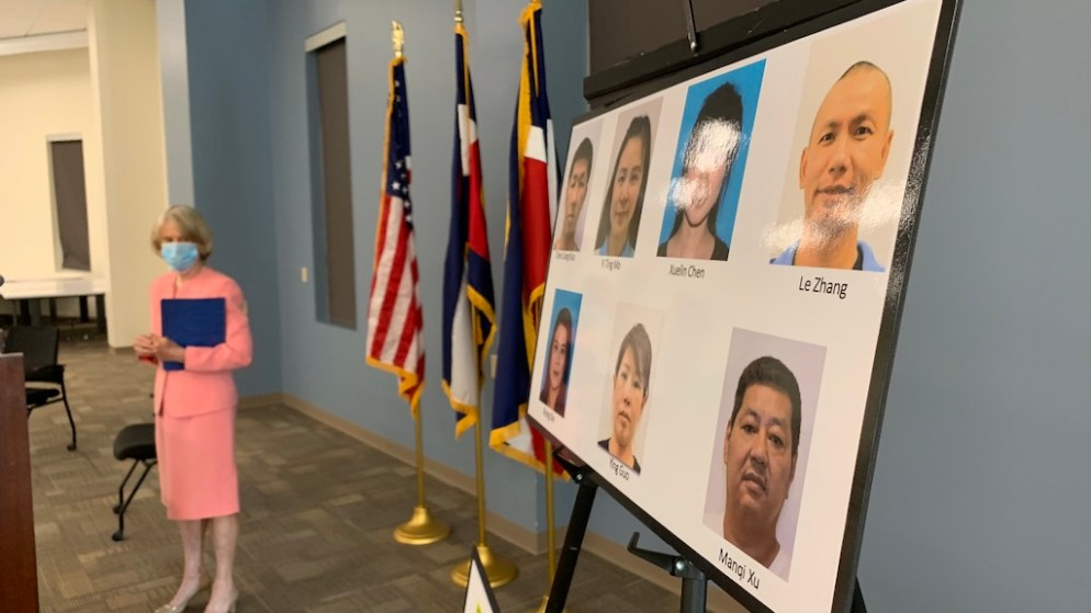 Denver District Attorney Beth McCann looks at a photos for seven Chinese nationals indicted on human trafficking charges in Colorado after a press conference on Thursday, August 20, 2020, in Denver. (Esteban L. Hernandez/Denverite)