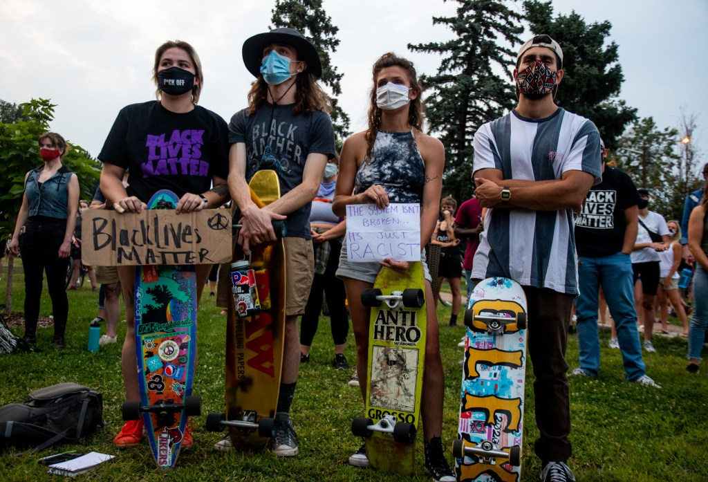 "From left, Lexie Sievert, Luke Foltz, Arianna Schwab and Teagan Glass hold their signs and skateboards during the ""Protect Black Men: Colorado Action for Jacob Blake"" gathering at Manual High School in Denver."