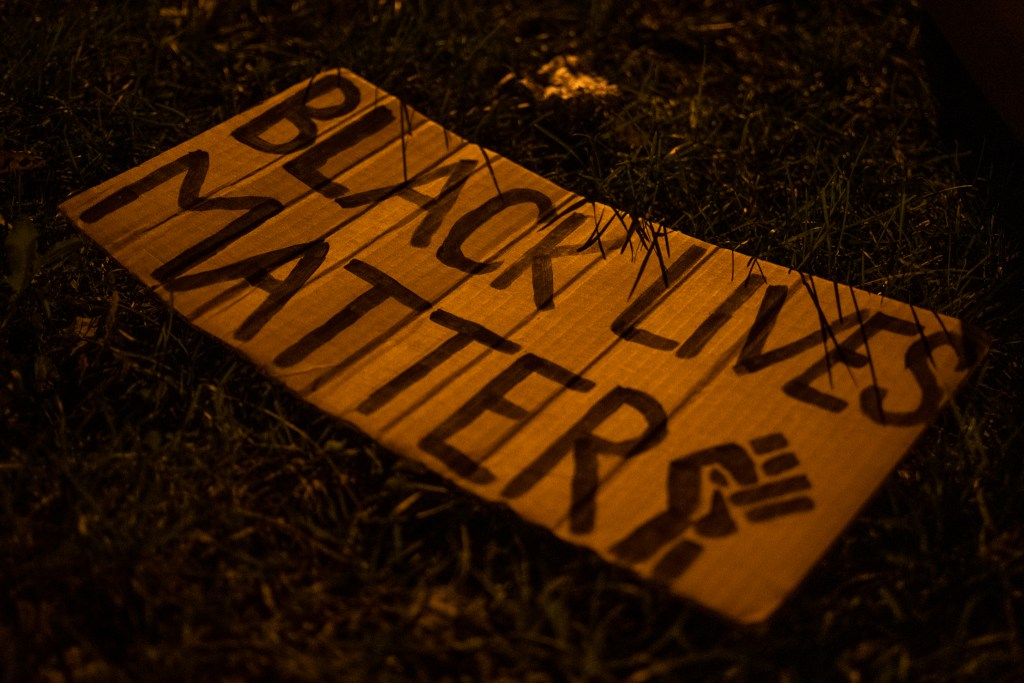 "A Black Lives Matter sign rests on the grass after the ""Protect Black Men: Colorado Action for Jacob Blake"" gathering at Manual High School in Denver."