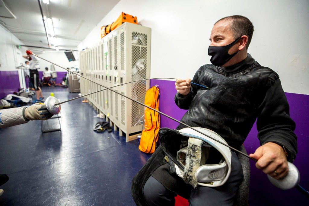 Nathan Anderson, head coach and owner of the Denver Fencing Center, helps calibrate a parafencing rig in his Ruby Hill gym. Sept. 1, 2020.