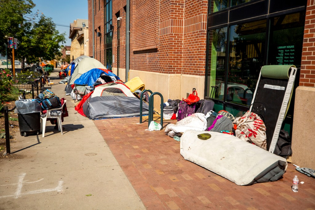 An encampment along the side of the Blair-Caldwell African American Research Library on Welton Street in Five Points. Sept. 30, 2020.