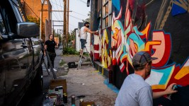 Sie, right, and Keith Jive, center, paint as Brooke Juno looks at her wall from afar in a River North Art District alleyway on Sept. 17, 2020.