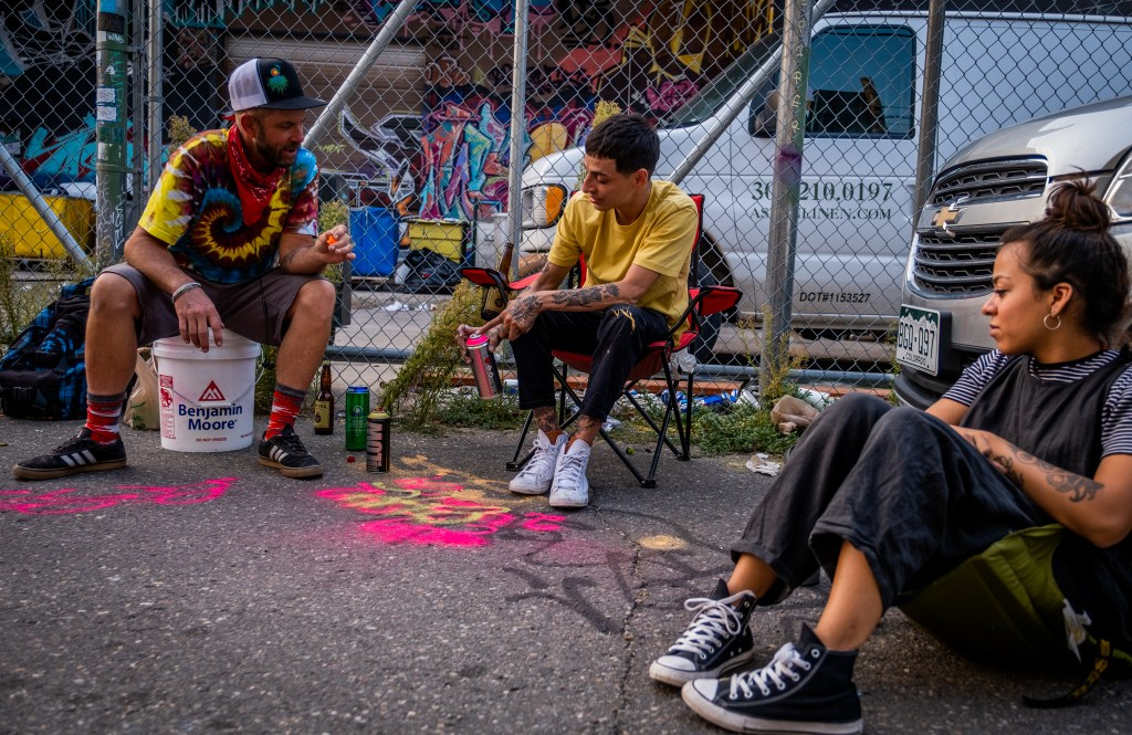 From left, Jethro, Milo and Margarita discuss different paints in a River North Art District alleyway on Sept. 17, 2020.