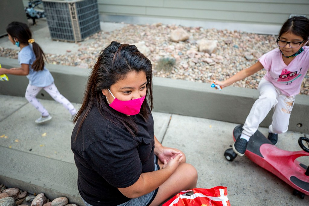 Noemy Ruano sits outside of the Decatur Place Apartments, where she lives in Sun Valley, as her kids Aleah and Kimberly play around her. Oct. 1, 2020.