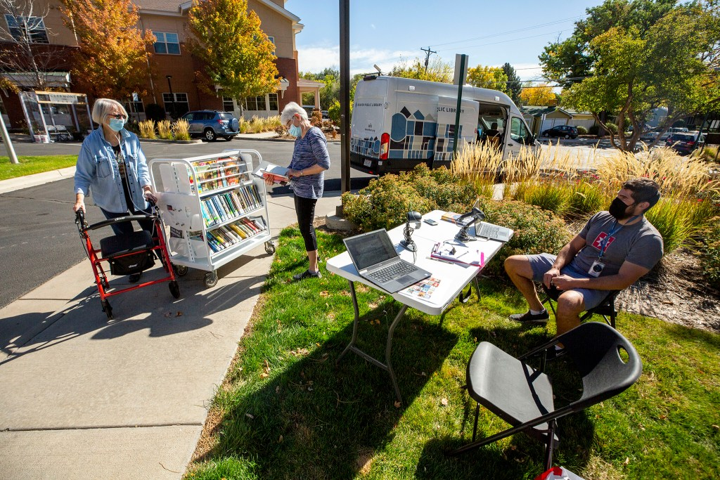 Claire McLane (left) and Alice Latta make use of the Denver Public Library's mobile bookmobile parked at Clermont Park in University Hills. Oct. 13, 2020.
