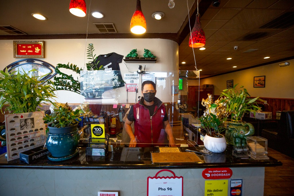 Lang Nhuyen, owner of Pho 96 Vietnamese Restaurant, at work behind a barrier and a facemask. Oct. 27, 2020.