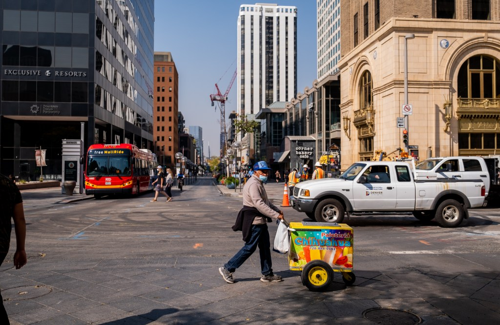 Delgado passes through the 16th Street Mall, watching out for security guards, while walking to a convenience store to buy lunch and water on Oct. 8, 2020. Since he's not allowed to sell on the mall and has been kicked out by security before, he feels on edge when in the area.