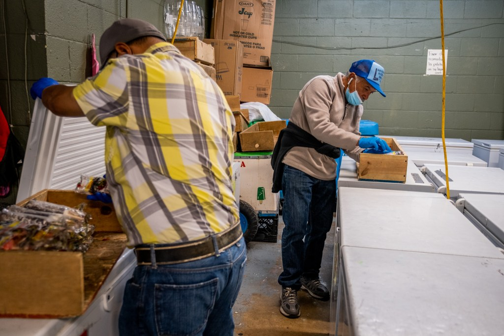 Delgado, alongside another paletero, gets popsicles for the day's sales in the back of Paletería Chihuahua in Cole on Oct. 8, 2020.