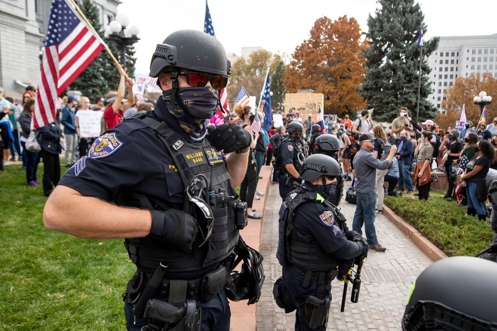Colorado State Troopers stand in between supporters of Joe Biden and Donald Trump rallying at the Capitol. Nov. 7, 2020.