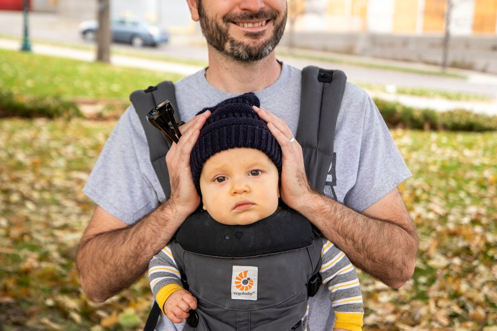 Will Montague sheilds baby Oscar's ears as people driving around the Colorado Capitol honk endlessly in celebration of Joe Biden's victory in the U.S. presidential election. Nov. 7, 2020.