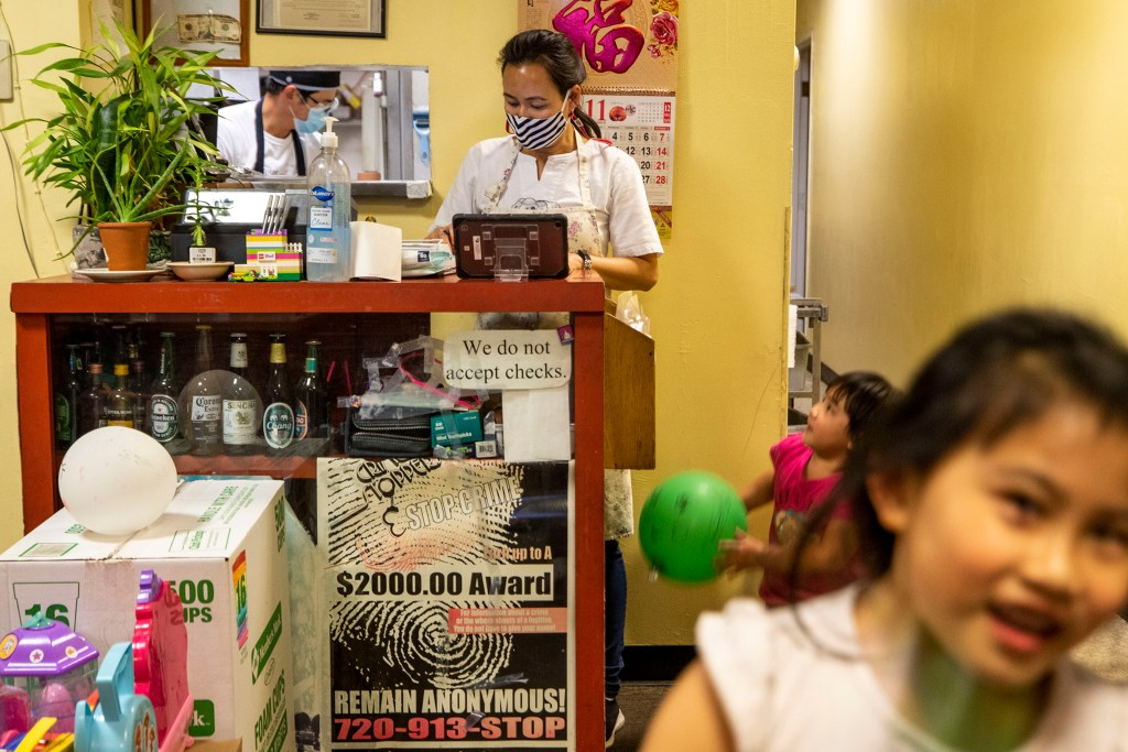 Prince and Lek Nuntanavooth work the dinner rush at J's Noodle and Star Thai Delivery as their daughters, Pan and Pat, bounce around the dining room that's become their playplace. Nov. 8, 2020.