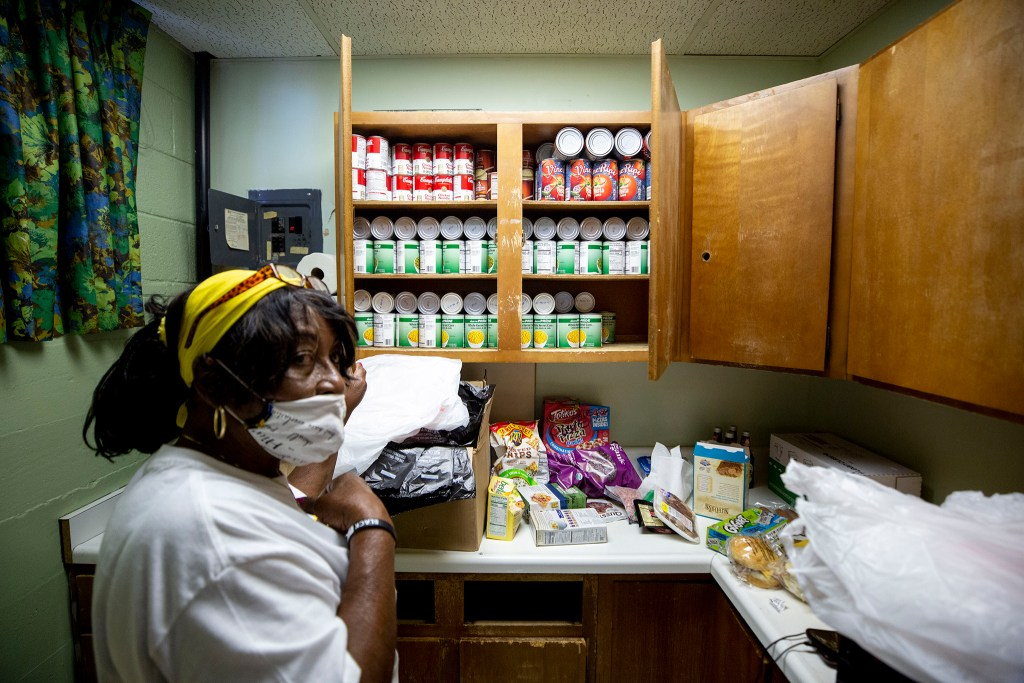 Rose Milon, director of the Epworth United Methodist Church's food pantry, shows some of the stores in the pantry's Bruce Randolph Avenue headquarters. July 23, 2020.