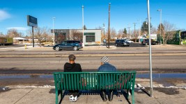 "Kristy Jo Gower, right, waits for a bus with someone she just met on East Colfax Avenue, Nov. 25, 2020. Gower said she'd spend a million dollars on helping people experiencing homelessness, like herself. ""They need help to stand up,"" she said. ""They don't need a kick in the teeth."""