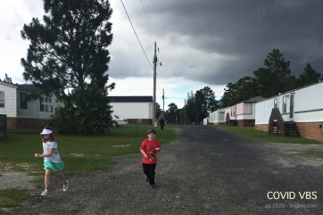 """Each day, we """"raced"""" up to the main street for exercise. You can see me with Caroline in the distance. The older kids ran extra fast this day; maybe they were anxious about the coming rain storm!"""