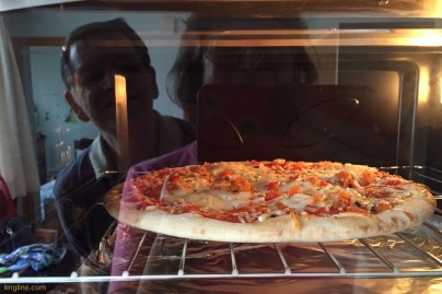 Notice the reflection of our happy faces as our first meal (a frozen pizza from Italy--cheapest we could find!) bakes in our new oven!