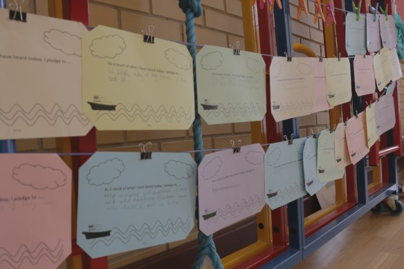 Stakeholder pledges displayed on a washing line strung up on the climbing frame in the school hall