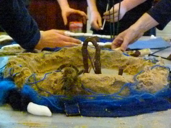 four sets of hands working on the 3D model made with sand, clay, blue wool and felt material.