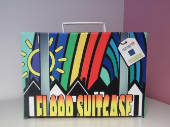 A brightly coloured suitcase with the words 'Flood Suitcase' written on it in big letters