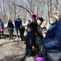 St. Olaf students and youth campers stand in a circle along a wooded path at River Bend Nature Center.