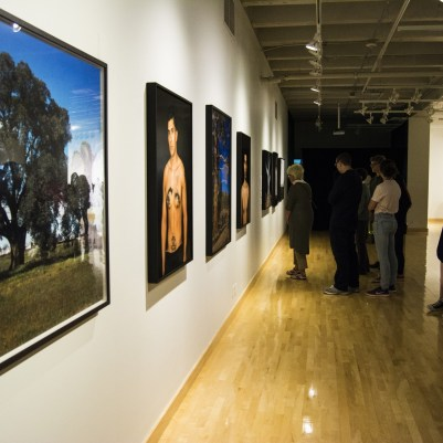 Museum attendees view works from Gonzales-Day's Searching for California Hang Trees and Memento Mori series.
