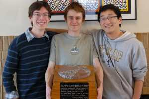 """St. Olaf students (from left) Nick Gantt '15, Warren Shull '13, and Boyang Wei '13 captured the coveted """"pizza trophy,"""" a granite sculpture of the """"pizza"""" theorem and its proof."""