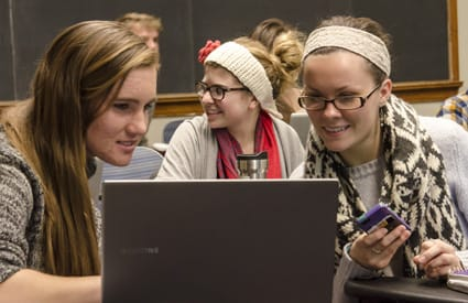 St. Olaf students Amy Mihelich '16 (left) and Emma Youngquist '15 work together during their political science class at Carleton.