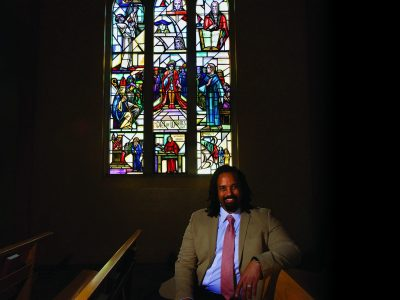 Religion Professor Anthony Bateza poses with stained glass window in Boe Memorial Chapel that traces the history of the Reformation.