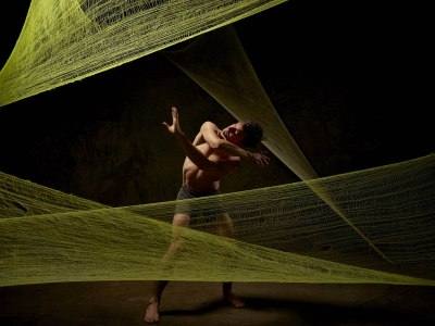 St. Olaf dance major Timmy Wagner '11 in a dance performance surrounded by web-like green fabric.