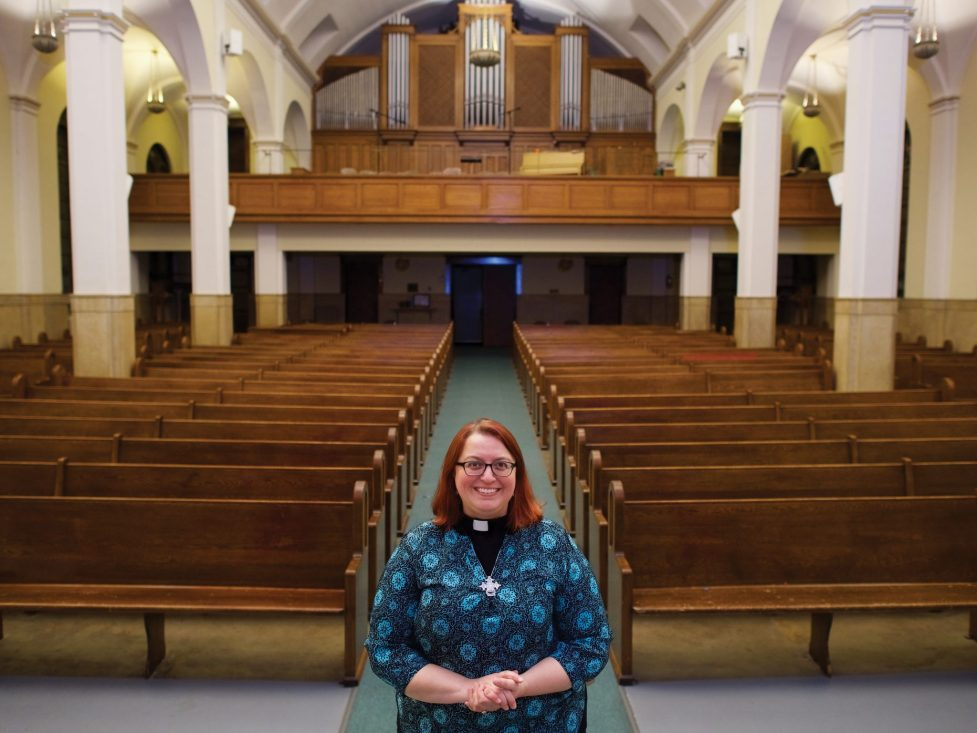 Woman standing in front of pews in a chapel.