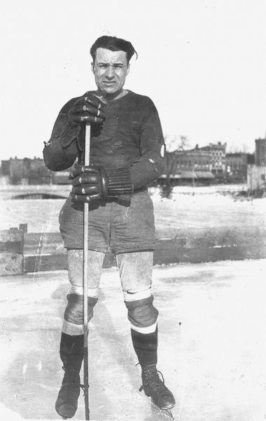 "Harold ""Chick"" Hagen stands on ice rink with hockey gear"