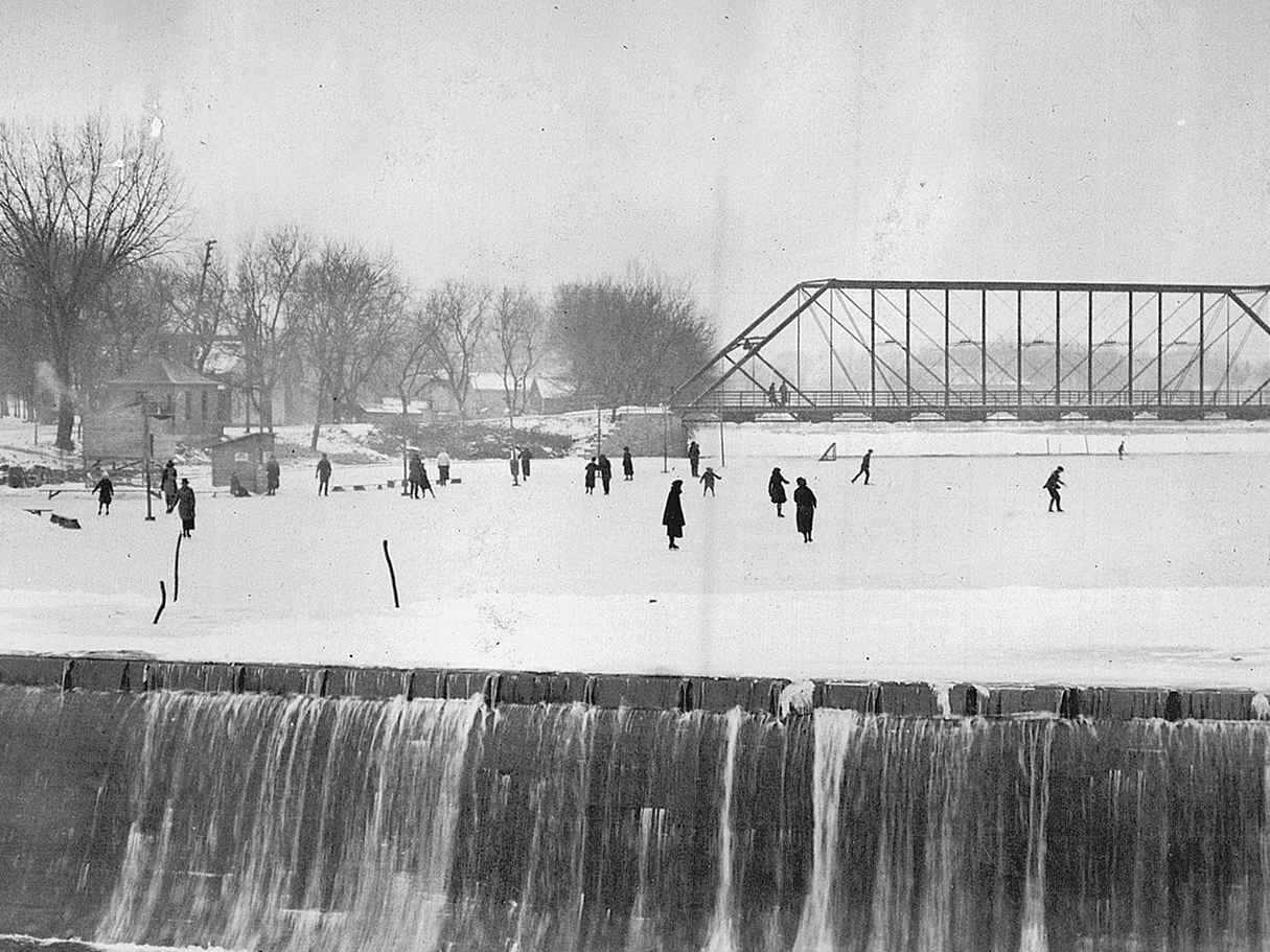 Skaters on the Canon River with waterfall in foreground and iron bridge in background