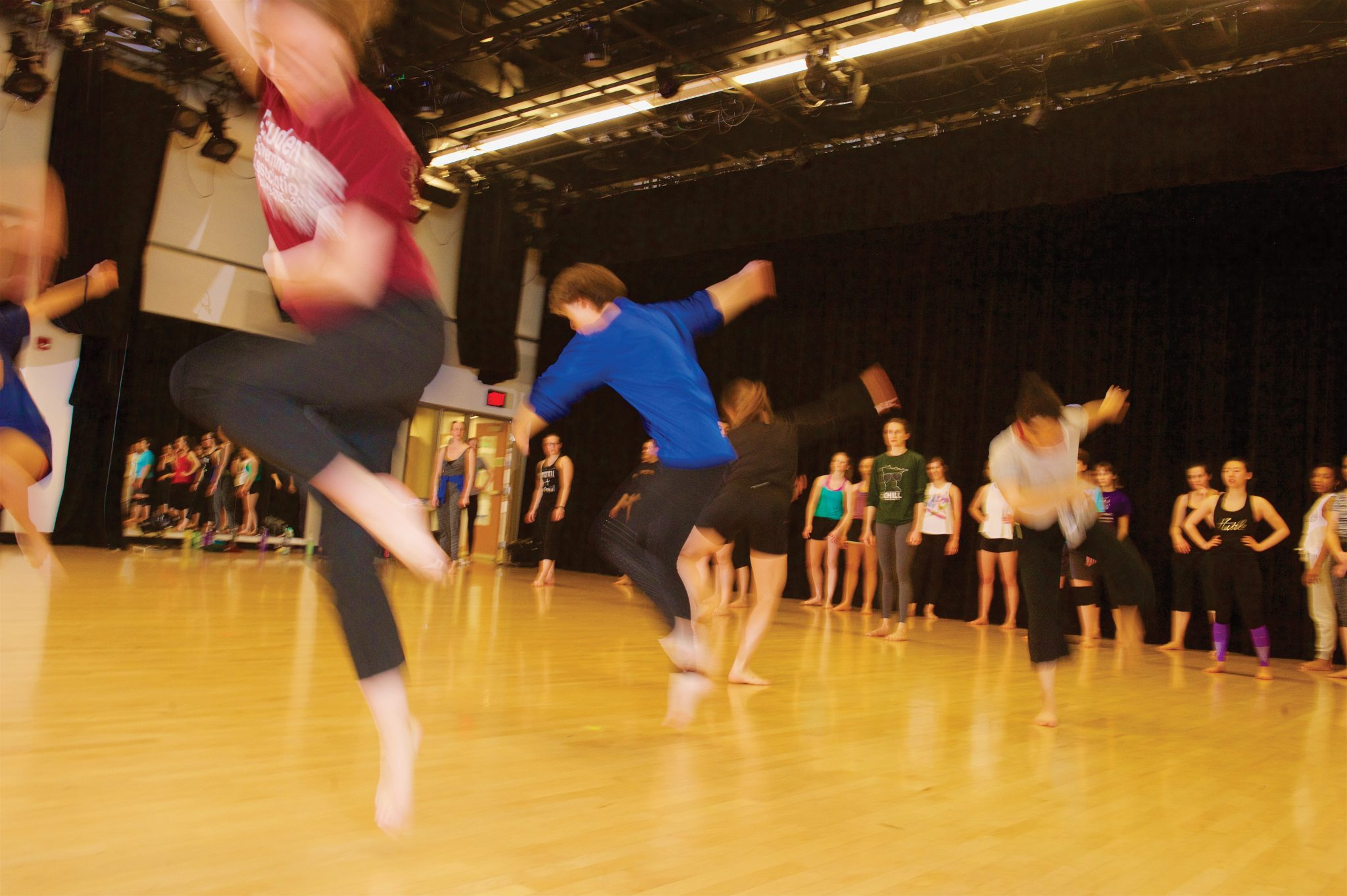 Blurred dancers in a large practice room.