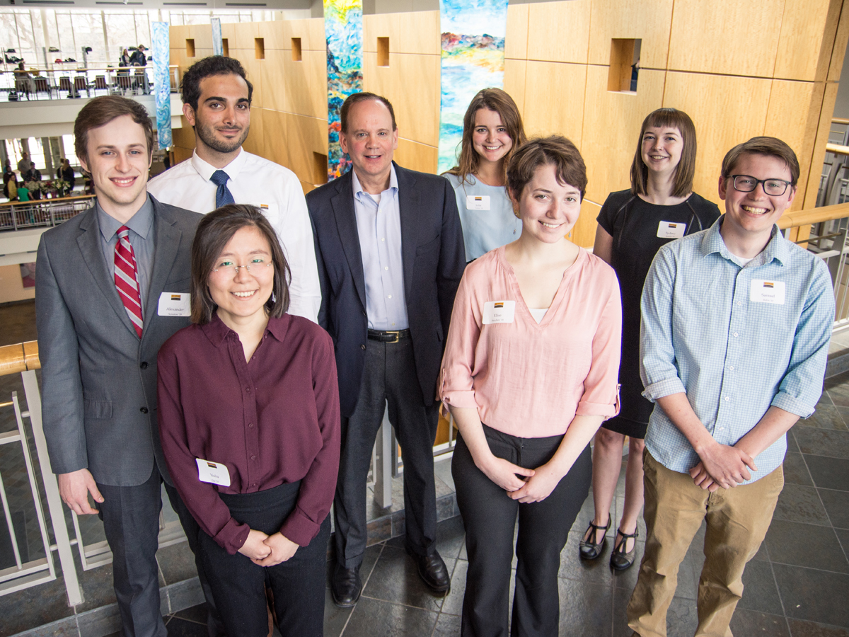 Paul Svoboda stands in Buntrock Commons with seven past participants of the Svoboda Legal Scholars Summer Program.
