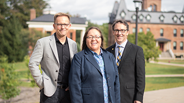 2018 Alumni Award recipients Wendy Helgemo '91, Craig Hella Johnson '84, amd Jon Hallberg '88 stand in front of Old Main.