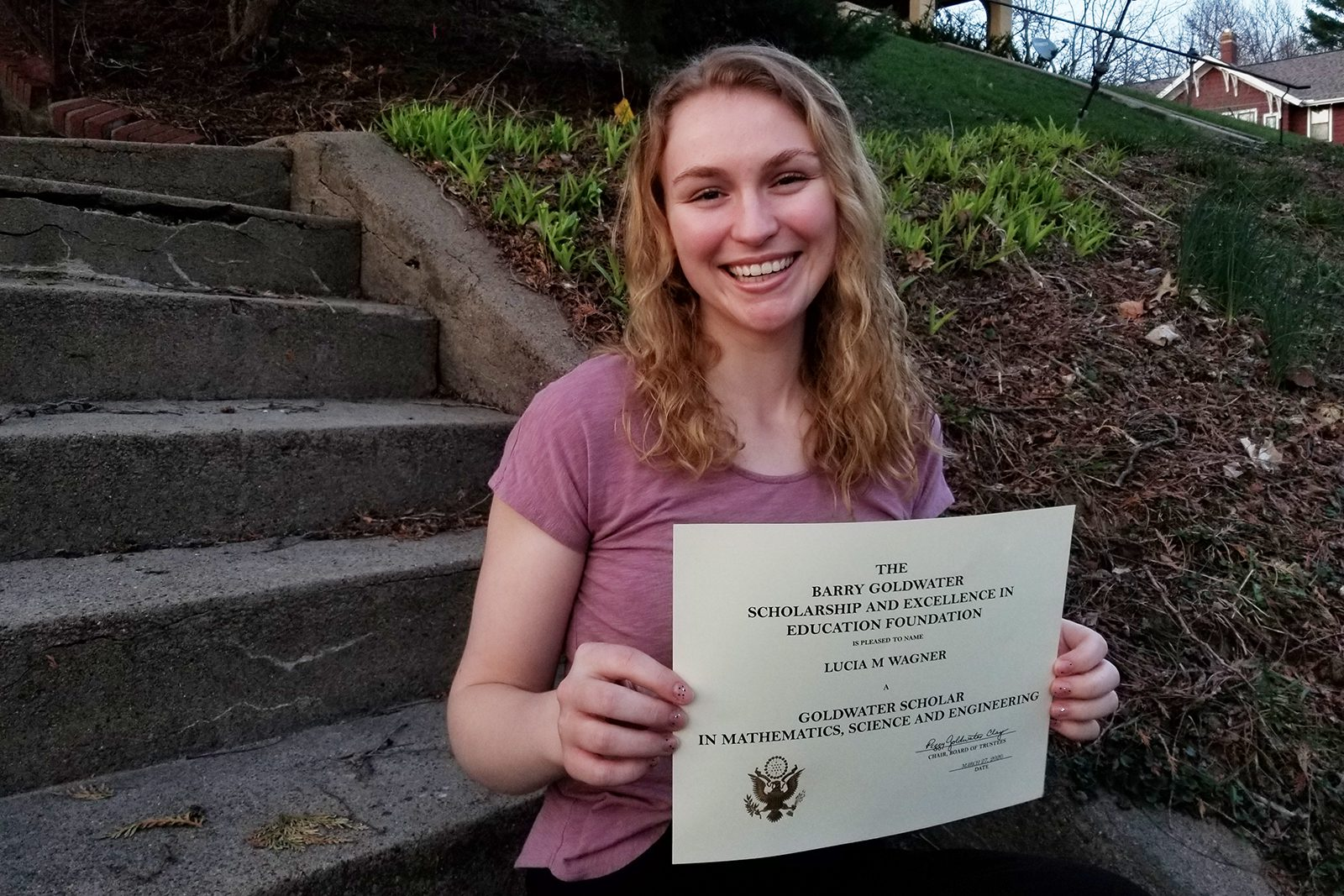 Lucia Wagner holds her scholarship certificate.