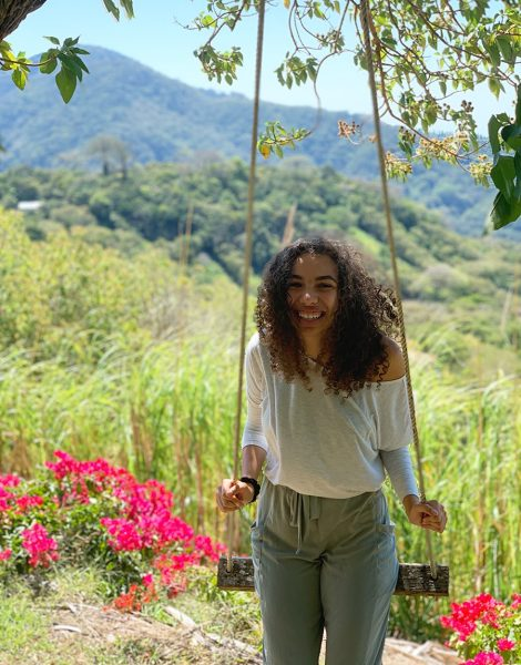 Portrait of student naturalist Izzy Istephanhous on a swing in front of flowers, grass and mountains.