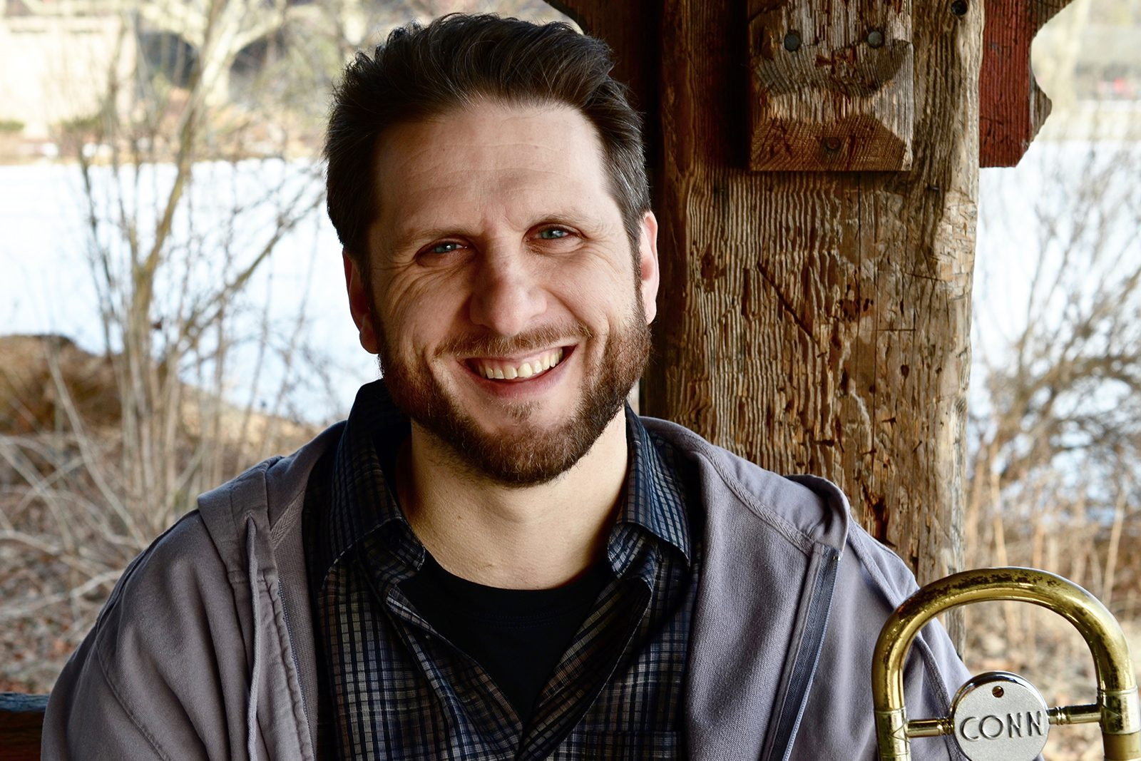 Portrait of St. Olaf jazz professor and conductor JC Sanford with his trombone outside near a wooden post, trees, and a river.