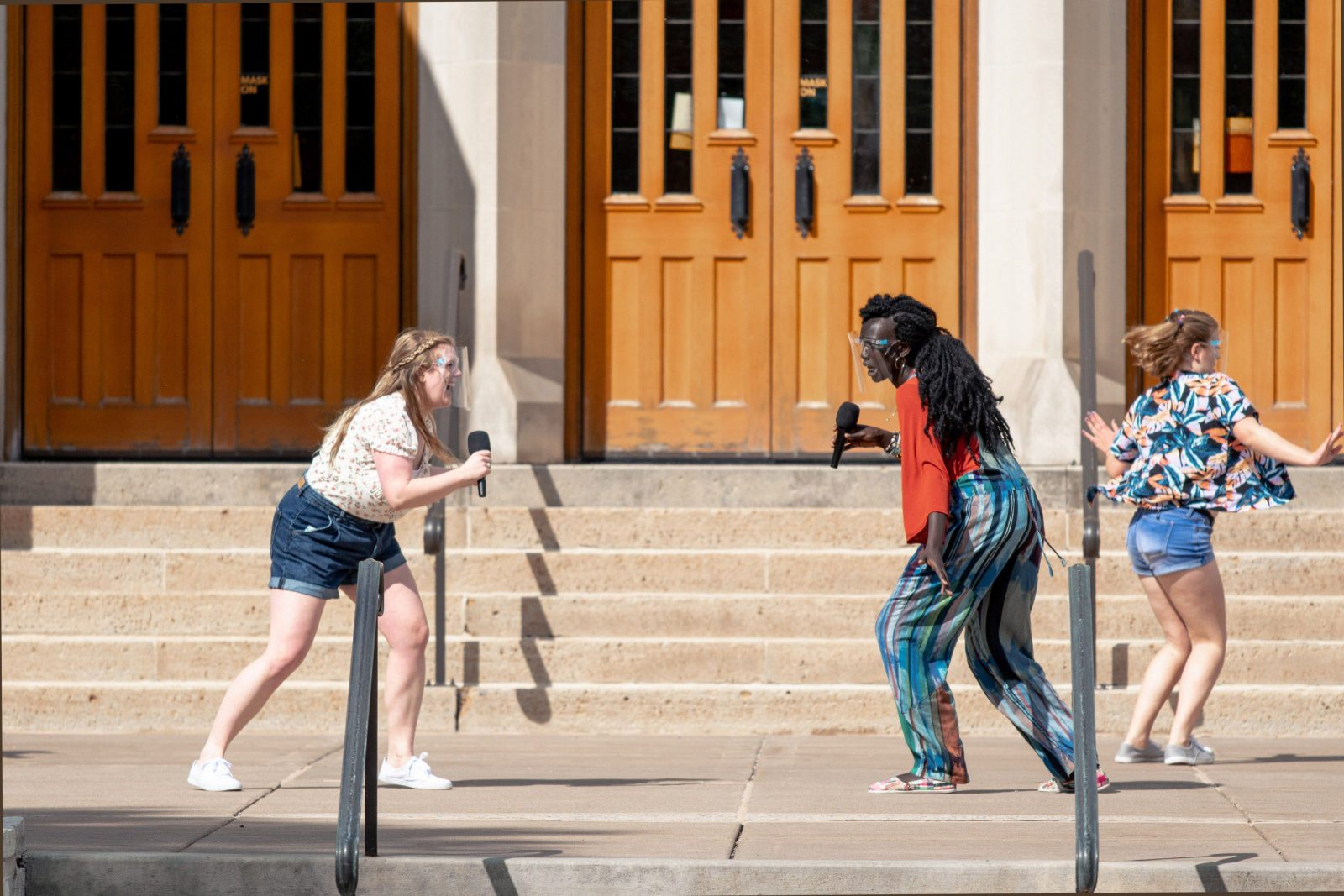 Tamsin Olson (left) and Mary Maker sing facing each other on the chapel plaza.