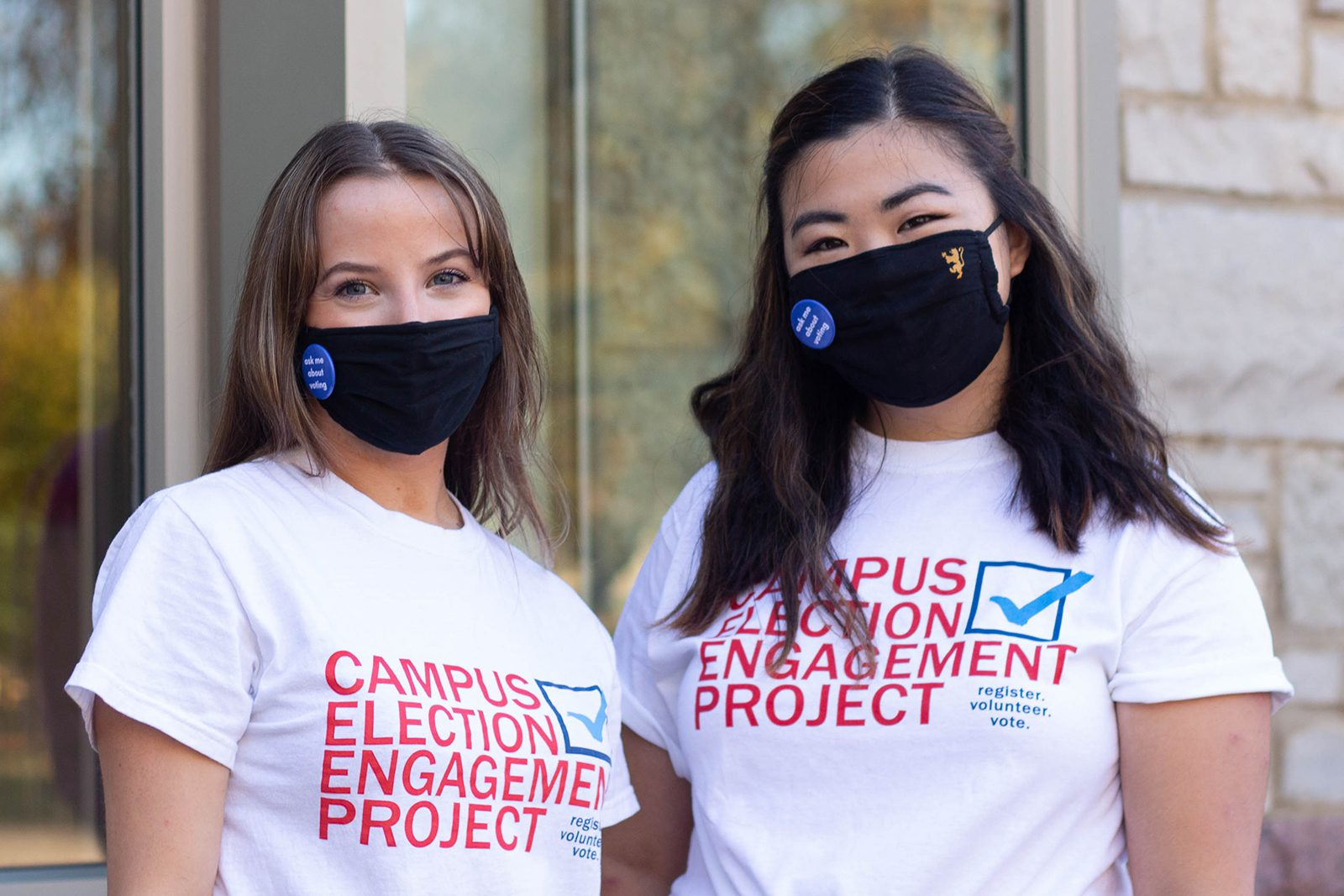 Portrait of Linnea Cheek (left) and Hannah Liu wearing masks in front of a window and limestone wall.