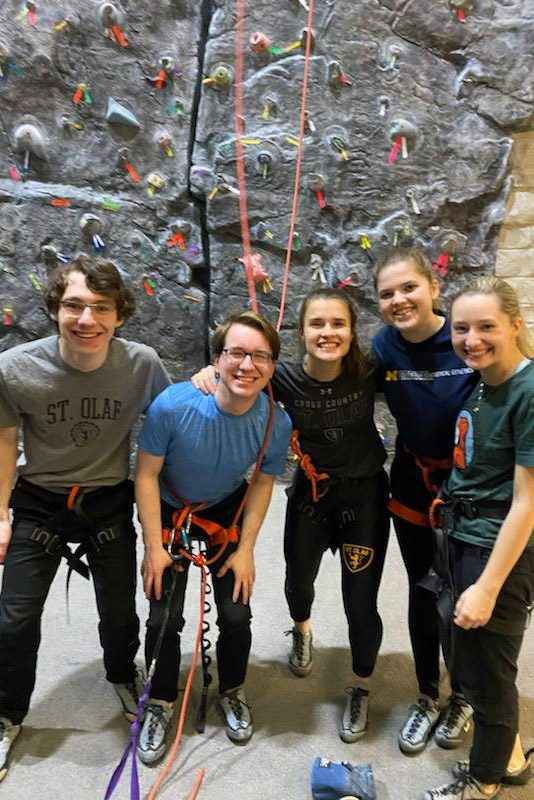 Portrait of (left to right) Michael Daly, Jack Wolf, Lisa Fisher, Martha Barnard, and Victoria Knutson wearing climbing gear in front of a climbing wall.