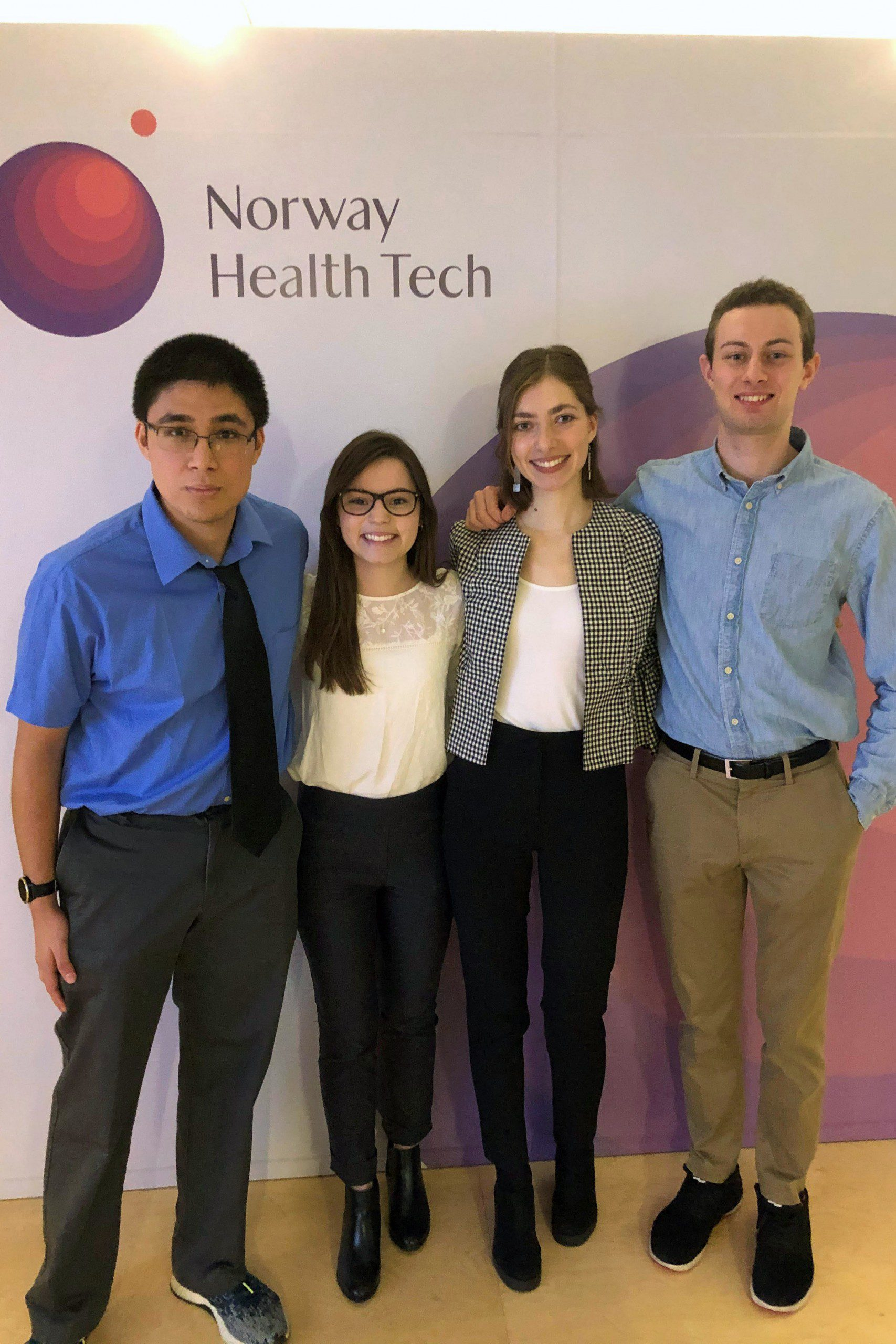 Norway Innovation Scholars stand in front of a wall with the Norway Health Tech logo.