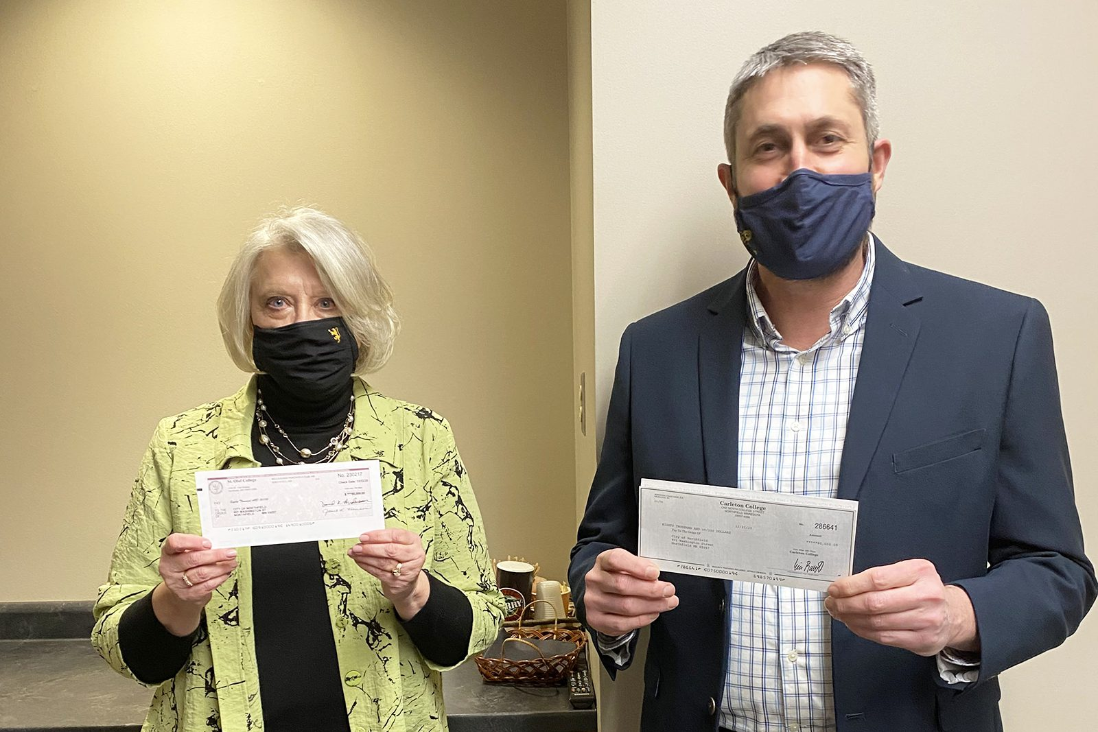 St. Olaf Vice President and Chief Financial Officer Janet Hanson and Carleton Vice President and Treasurer Eric Runestad pose for a photo with the checks they gave to the City of Northfield.