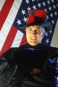 A portrait of Jim Farrell wearing a hat and posed in front of the American flag.