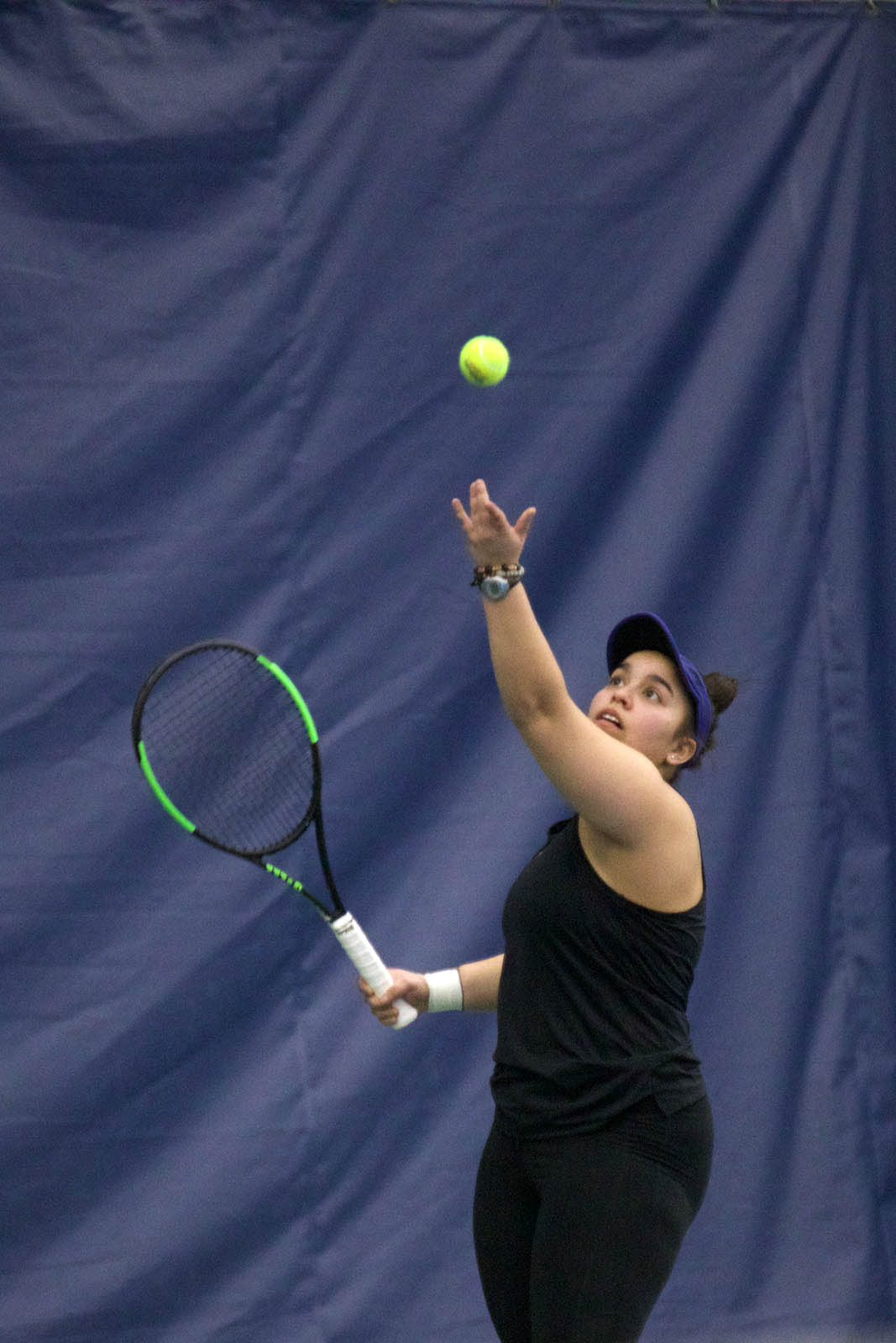 Sabrina Barboza holds her tennis racket and throws a tennis ball upwards in a serve with a blue curtain in the background.