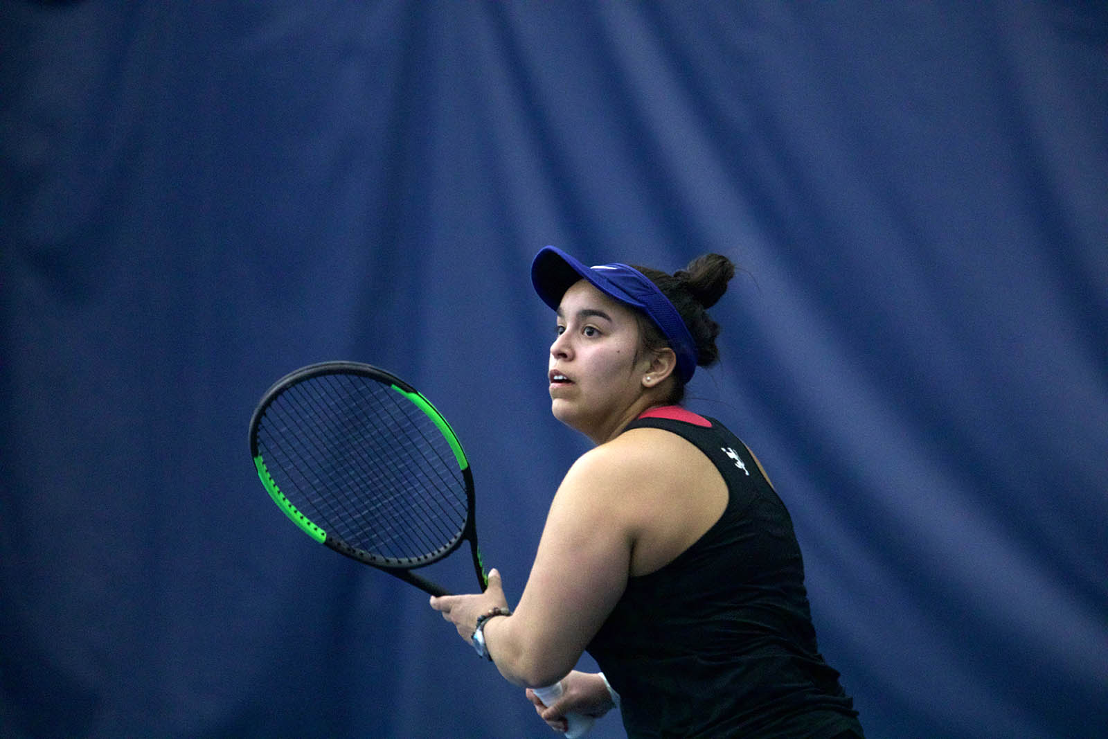 Sabrina Barboza holds a tennis racket during a game with a blue curtain in the background.