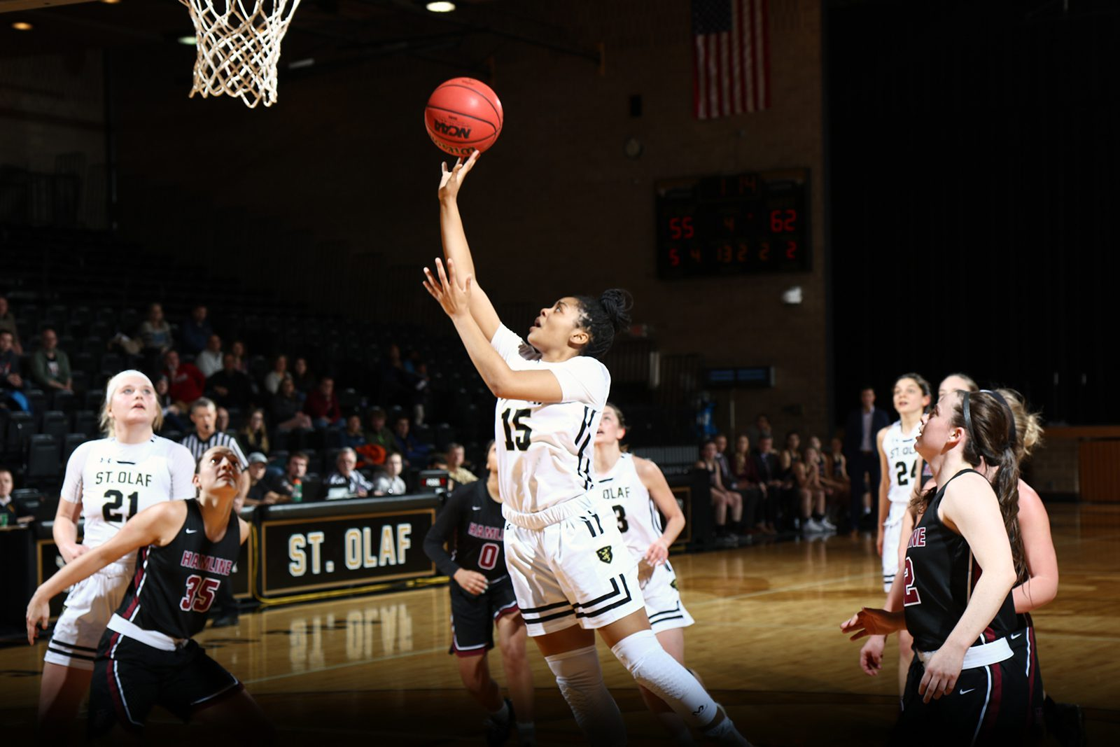 K'Lynn Lewis lifts a basketball up to the net while other players stand near her on the court.