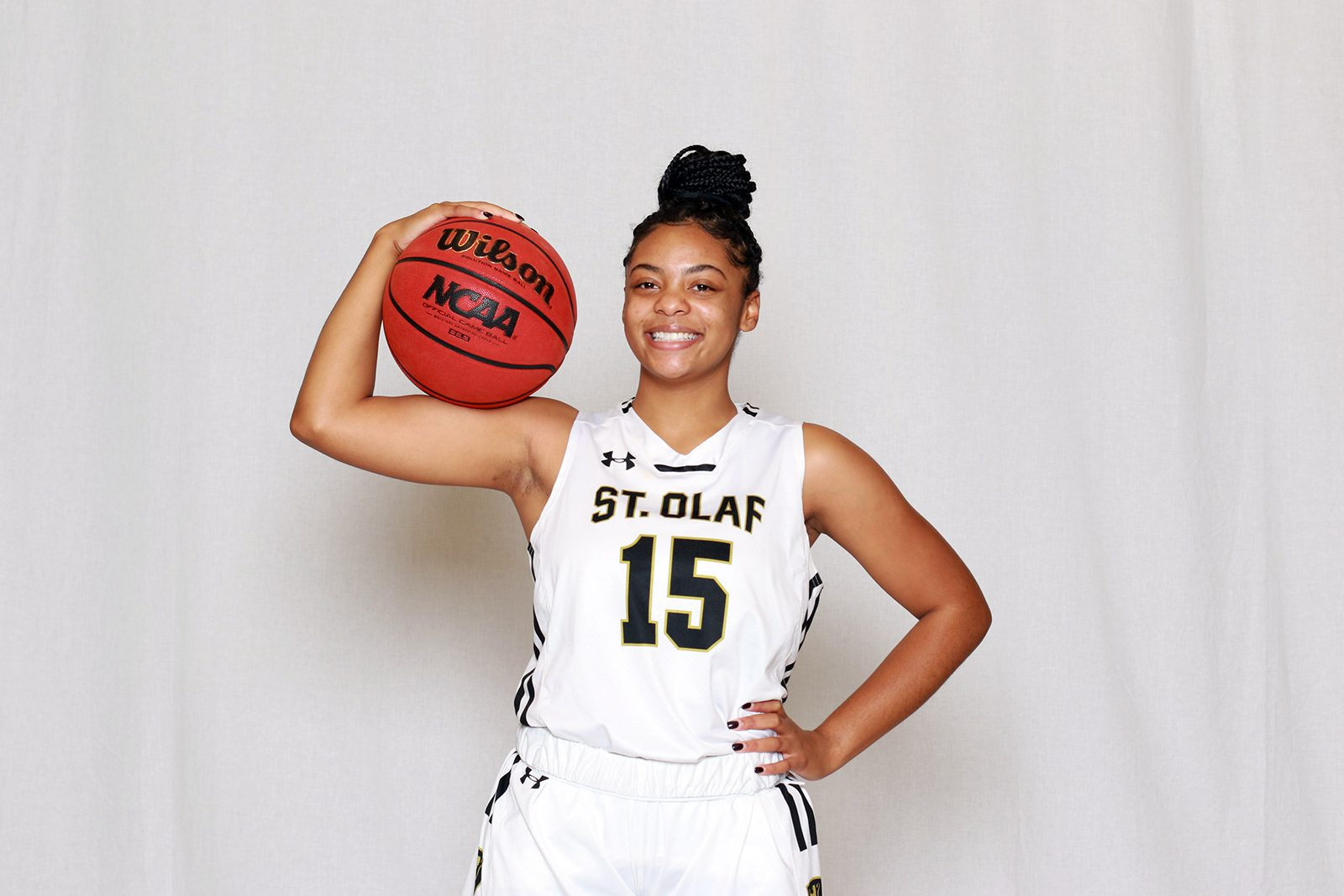 Portrait of K'Lynn Lewis wearing a white basketball jersey and holding a basketball against a white background.
